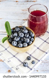 Fresh blueberry in wooden cup and glass of berry juice with wooden background.