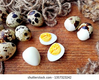 Fresh & boiled quail eggs on wooden kitchen table. Sliced quail egg closeup macro yolk and white for healthy breakfast. Small quail eggs from organic farm. Diet food concept - two half cut whole egg