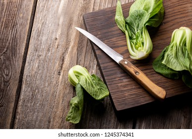 Fresh bok choy on wooden board with knife