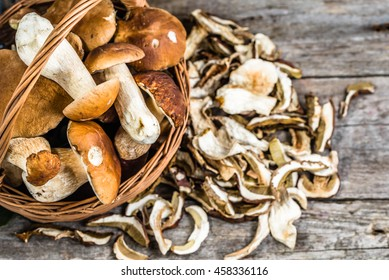 Fresh boletus mushrooms in a basket and dry mushroom on wooden table, overhead