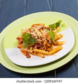 Fresh bolognese pasta in green plate over wooden board