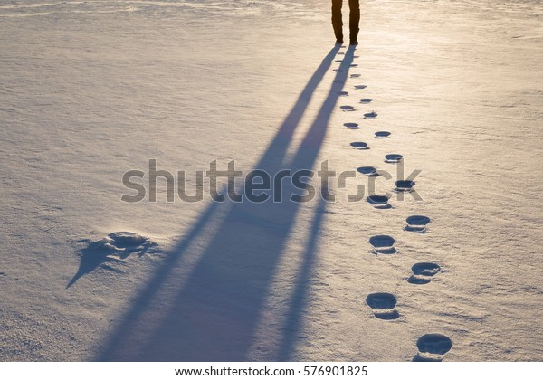 Fresh boots footprints with human shadow in the snow in the sunset light in winter evening. Background.