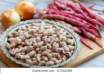 Fresh borlotti or cranberry beans on wooden background