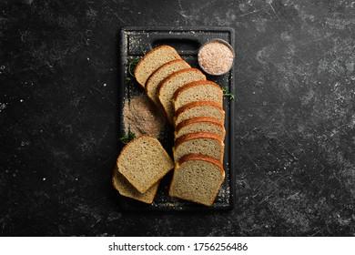 Fresh bran bread. Baking. Top view. Black stone background, rustic style.