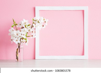 Fresh branches of cherry white blossoms in vase on table. Mockup for special offers as advertising or other ideas. Empty place for inspirational, motivational text or quote at soft pastel pink wall.