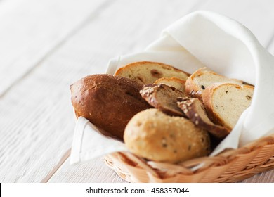 Fresh bread assortment on white wooden background, copyspace. Warm baked sweet products, served in rustic basket