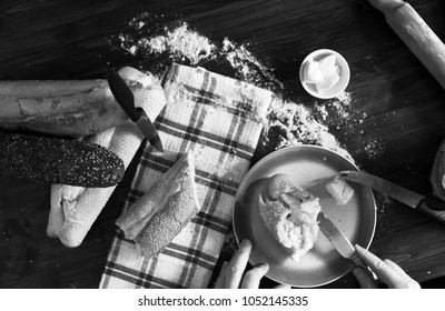 Fresh bread and baguettes on kitchen wooden work surface in black an white