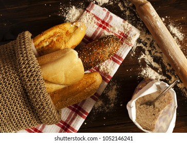 Fresh bread and baguettes on kitchen wooden work surface