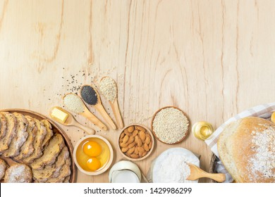 fresh bread, barley, almond nuts, flour, eggs, butter, bottle of oil, milk and different seeds on wooden background with free text space, top view.
