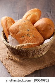 Fresh bread in the basket on wooden background