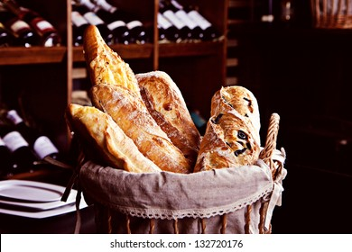 Fresh bread in basket witn bottles of wine on background
