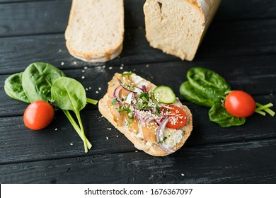 Fresh bread, fish and vegetables sandwiches. Food background, ingredients on the table. Healthy food, styling, cooking concept.