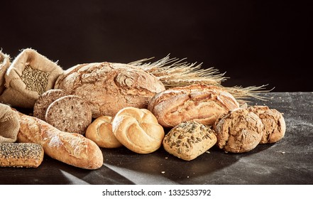 Fresh bread loaves assortment piled on dark table surface with grains of rye and wheat, against black background