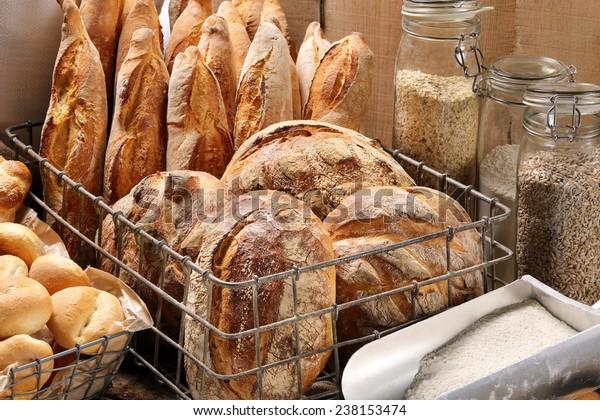 Frisches Brot in Metallkorb auf Bäckerei auf Holzhintergrund