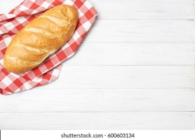 Fresh bread with napkin on kitchen table