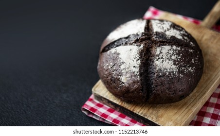 Fresh bread on black chalkboard background. Top view with copy space. Rye Bread on cutting board closeup