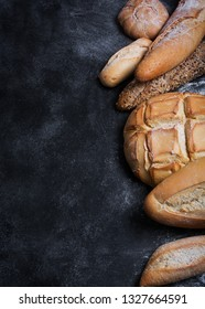 Fresh bread on black table. Top view with copy space, vertical orientation