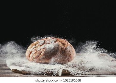 Fresh bread on table close-up in flour placer. Fresh bread on the kitchen table. The healthy eating and traditional bakery concept. Rustic style