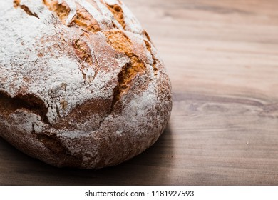 Fresh bread on wooden table with space for your text. Freshly baked traditional bread on wooden table.