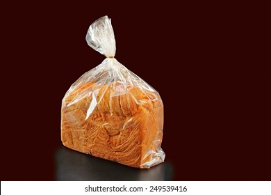 Fresh bread packaged in edible plastic bag on white background.