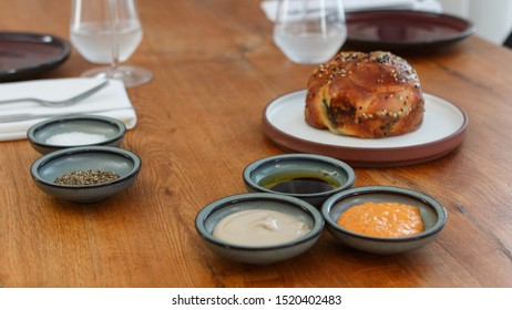Fresh bread, served on a flat round stoneware plate with a tall rim. Dip dishes on the side with salt, pepper and dips. Set on a wood table, with sharing plates, water and wine glasses, and cutlery.