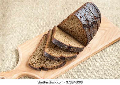 Fresh bread slice on wooden cutting board on burlap background