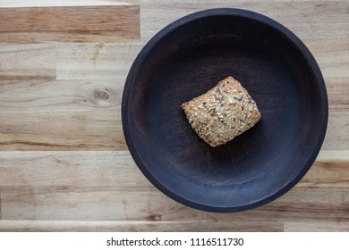 Fresh bread sprinkled with spices on a large wooden plate. The view from the top.