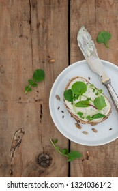 Fresh bread with vegan cream cheese and salad on an old wooden background