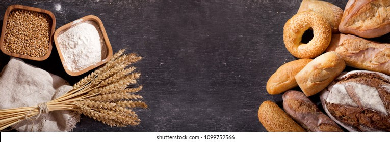 fresh bread with wheat ears and bowl of flour on dark board, top view