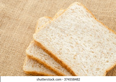 Fresh bread wheat on sack background.