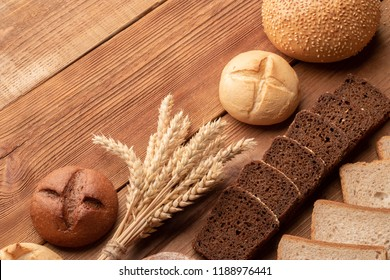 Fresh bread and wheat on wooden table. Top view with space for your text