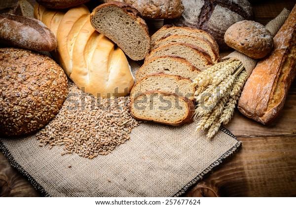 frisches Brot und Weizen auf Holz