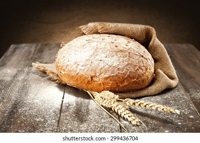 fresh bread and white fresh flour on dark brown top