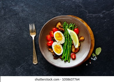 Fresh breakfast plate flat lay. Aspargus, tomatoes, mushrooms and eggs over black stone copy space background. Energy boosting food concept. Top view.