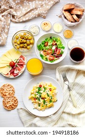 Fresh breakfast table. Healthy food. Top view. Scrambled eggs, salad, cheese, prosciutto, coffee and juice. Concept of business or holiday breakfast.