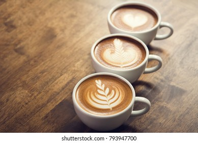 Fresh brewed coffees with beautiful latte art on surface, three cup in a row on wooden table ready to drink