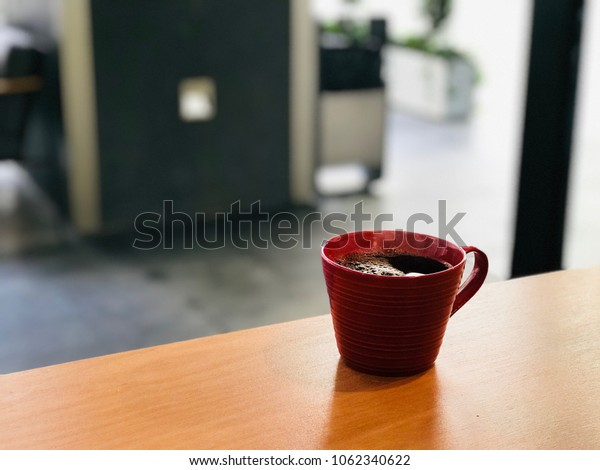 Fresh Brewed Steaming Filter Coffee in Red Cup at Cafe Shop