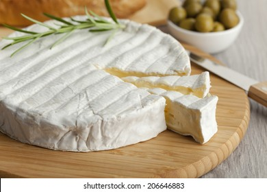Fresh Brie cheese and a slice close up