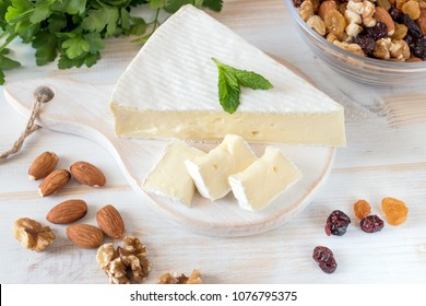 Fresh Brie cheese and a slice on a wooden board with nuts