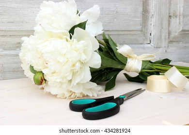 Fresh bright bouquet of white peony with scissors and satin ribbon on aged white wooden background. floral decor elements in a rustic setting