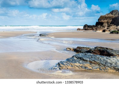 A fresh bright and breezy day in a quiet sandy cove on the North Cornish coast with sand, pools and rocks in the foreground.