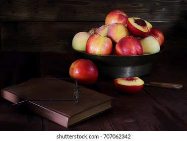 Fresh bright peaches and nectarines in a copper dish on dark wooden background