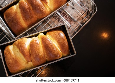 Fresh brioche bread on black table top with copy space. Top view.