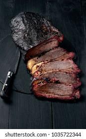 Fresh Brisket BBQ beef sliced for serving against a dark background