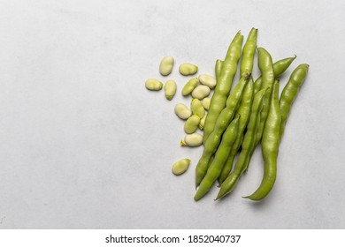 Fresh broad beans. Vertical shot with white rustic background