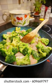 Fresh broccoli and chicken meat pieces in a frying pan in soft focus