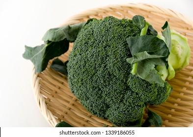Fresh broccoli on bamboo colander on white background