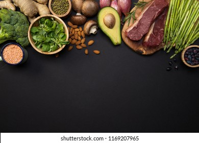 Fresh broccoli, veggies, beef steak top view. Ginger, avocado, asparagus, lentils, basil, almonds, beans, berries, mushrooms and onions on black background with copy space. Concept of healthy food.