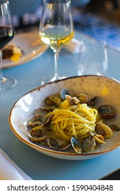 fresh bronze-drawn spaghetti and a sprinkling of parsley and Cilento oil with a glass of wine in a luxury Italian restaurant