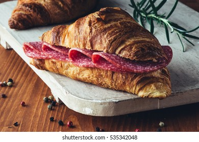 fresh brown croissant with salami on rustic table